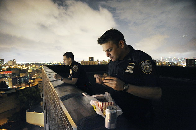 Officers spend their dinner break on a housing project roof.