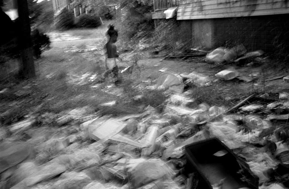 A child runs through garbage in the driveway of the abandoned house adjacent to his home.