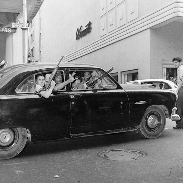 These young rebels are shown training a variety of weapons out windows of one of numerous cars that ranged Havana's streets, January 2, 1959, in the unrest attending plans for inaugurating a revolutionary government.