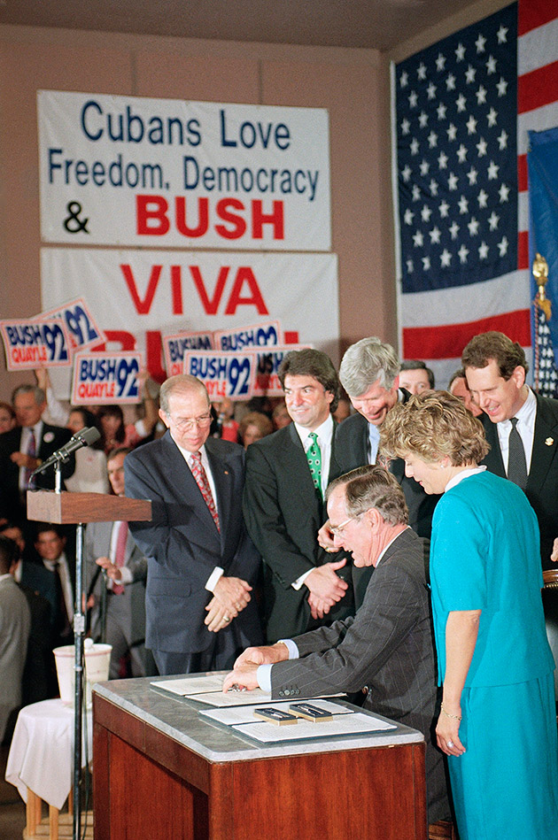 U.S. President George H. Bush signs legislation in Miami, Friday, Oct. 23, 1992 that will tighten the embargo on Cuba. The President is surrounded by supporters in Miami as he signed the bill that he said would