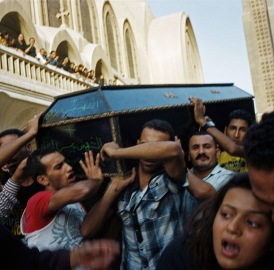 Relatives of victims carry coffins out of the Abbasiya Cathedral to be buried following violence that took place in front of the Maspero TV building on October 9 and 10, 2011. The clashes, which resulted in 28 deaths and left 212 injured, occurred between Copts demonstrating peacefully against an attack on a church in Upper Egypt and the Egyptian Army and security forces. The Copts were violently dispersed by tanks and armored vehicles, as well as random shooting in the crowd.