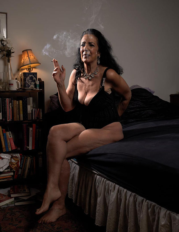 Woman sitting on edge of bed smoking