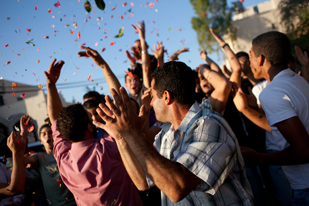 Men from the town of Wadi Fukin participate in a wedding celebration.