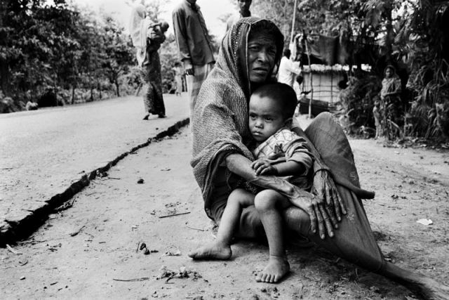 Rohingya Woman and her Grandchild sit on the Side of the Road…