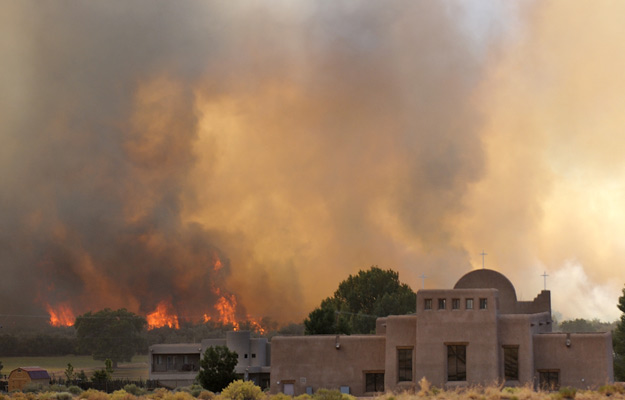 June 20, 2012 - A wildfire blazes behind St. Anthony Catholic Church in Sandia Pueblo, N. Mex.  Jim Thompson/Albuquerque Journal/ZUMAPress