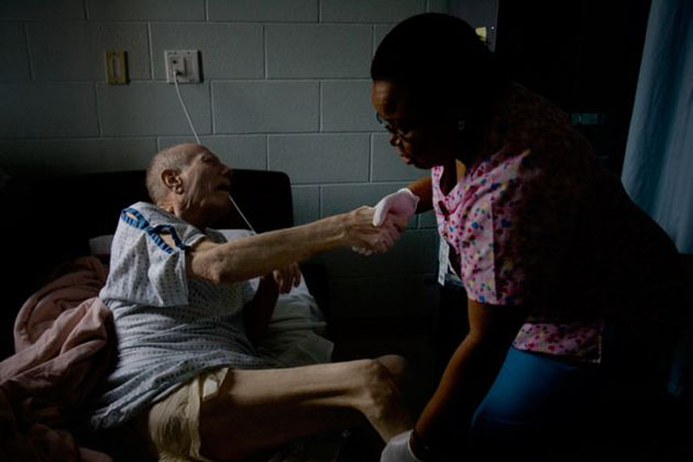 A prison nurse helps Charles Webb, then 74, into bed.
