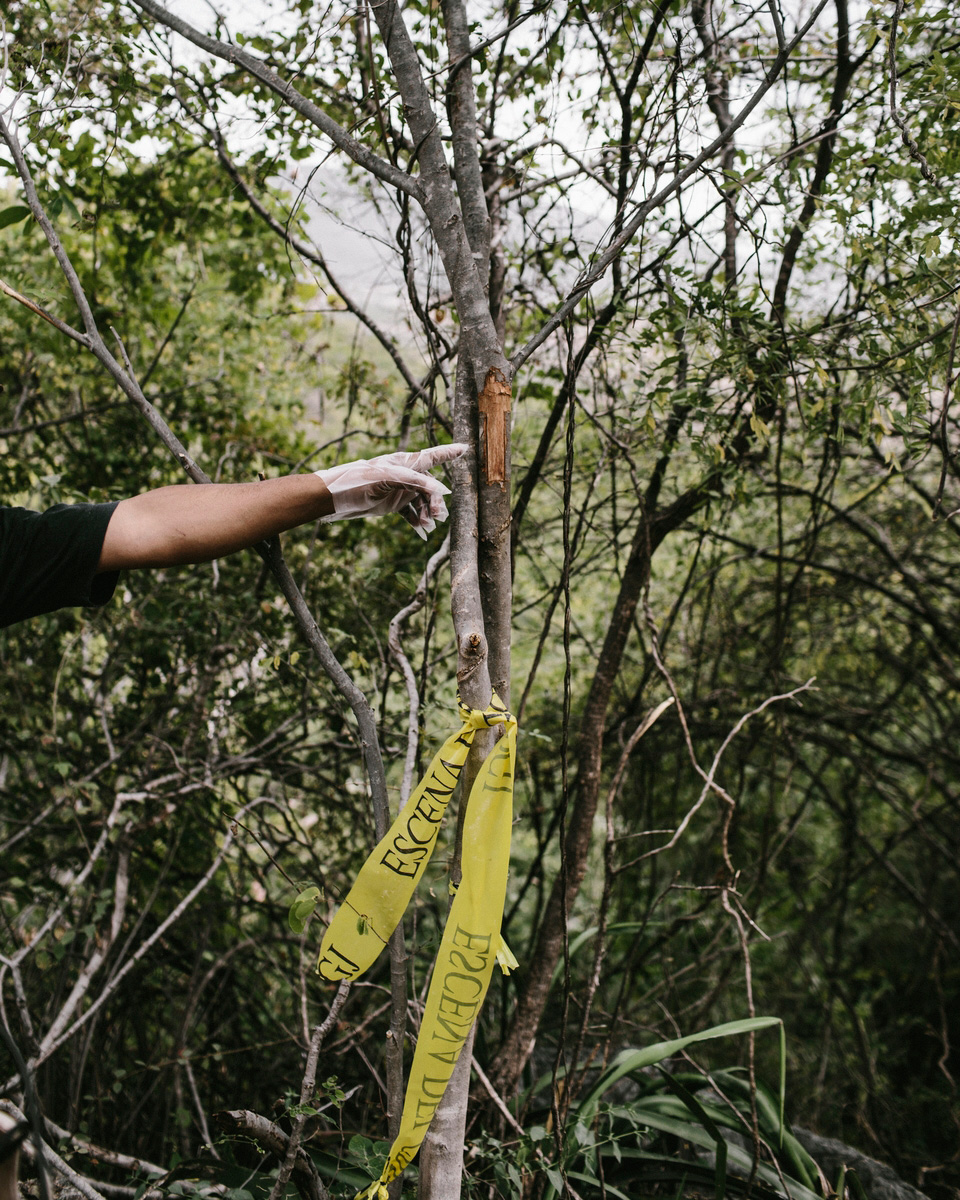 Miguel Angel Jimenez points at a cross etched in a tree trunk he thought to have been a criminal's last attempt at remorse at the grave site where 28 people were burned and buried.