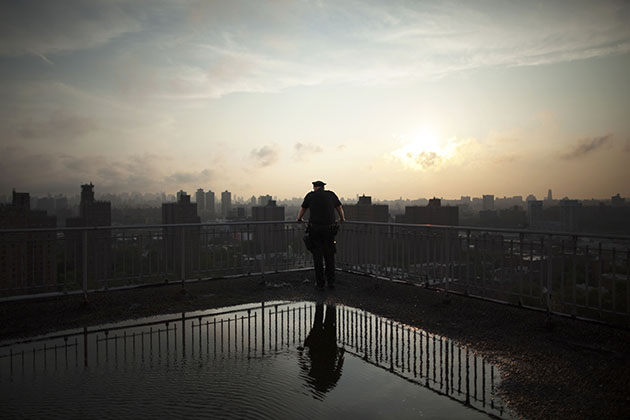 A rookie NYPD officer looks out over the Bronx from a rooftop.