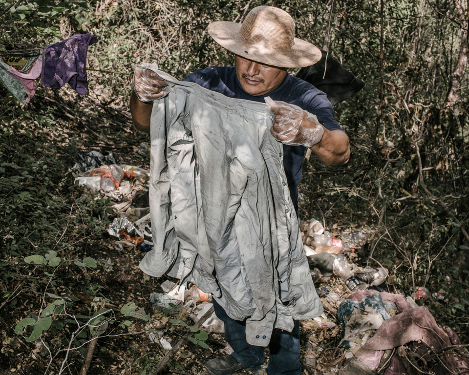 "These belongings and trash were found near a grave that was found outside of Iguala soon after the 43 students disappeared. At first authorities suspected the graves contained the students but DNA confirmed that none of the 28 bodies belonged to the students shedding light on the years of disappearances that have plagued Iguala. Here Miguel holds up a ""Manchester"" brand shirt in good condition."