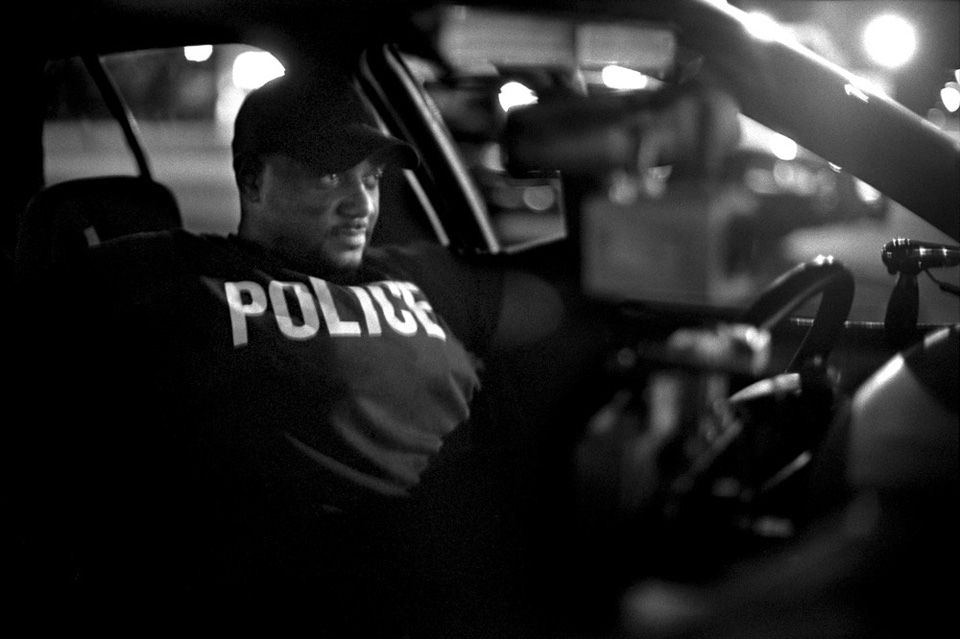 A wary Detroit police officer watches a crowd after an arrest on the East Side.