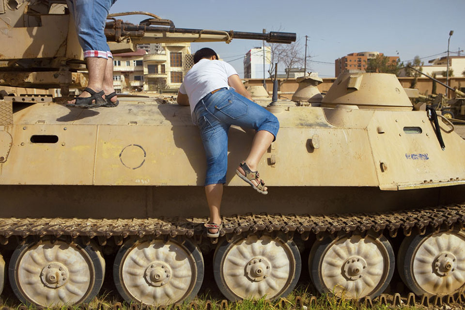 "A boy climbs on top of a tank at a museum housed in a former prison and military barracks in Sulaimani. Upon entering the museum, an inscription reads: ""We neither manufactured these weapons, nor feel proud exhibiting them. In fact, these were used by those who threatened our very existence. We also admit that these very weapons helped us achieve our freedom."""