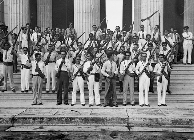 Students form revolutionary army in Havana, holding rifles on steps.