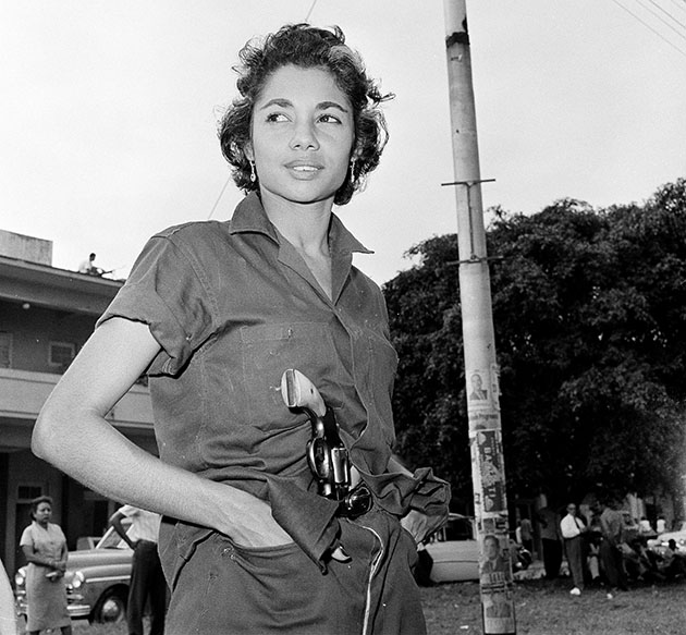 A young unidentified woman patrols near a headquarters building in Havana, Jan. 4, 1959.