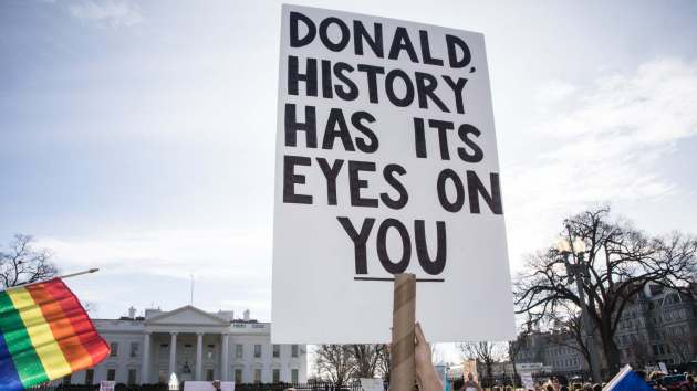 """A sign reads """"Donald, history has its eyes on you"""""""
