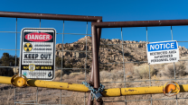 "With heaps of rock in the background, signs on a gate read ""Abandoned Uranium Mine, Keep Out"" with the symbol for radioactivity."