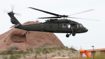 A Black Hawk helicopter takes off against a rust colored desert backdrop.