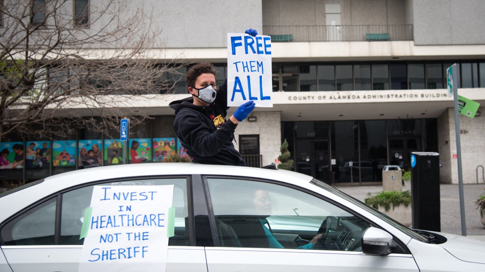 "A protestor in sweatshirt, cloth sick mask, and dark gloves holds a sign out the sunroof of a car, reading ""FREE THEM ALL."""
