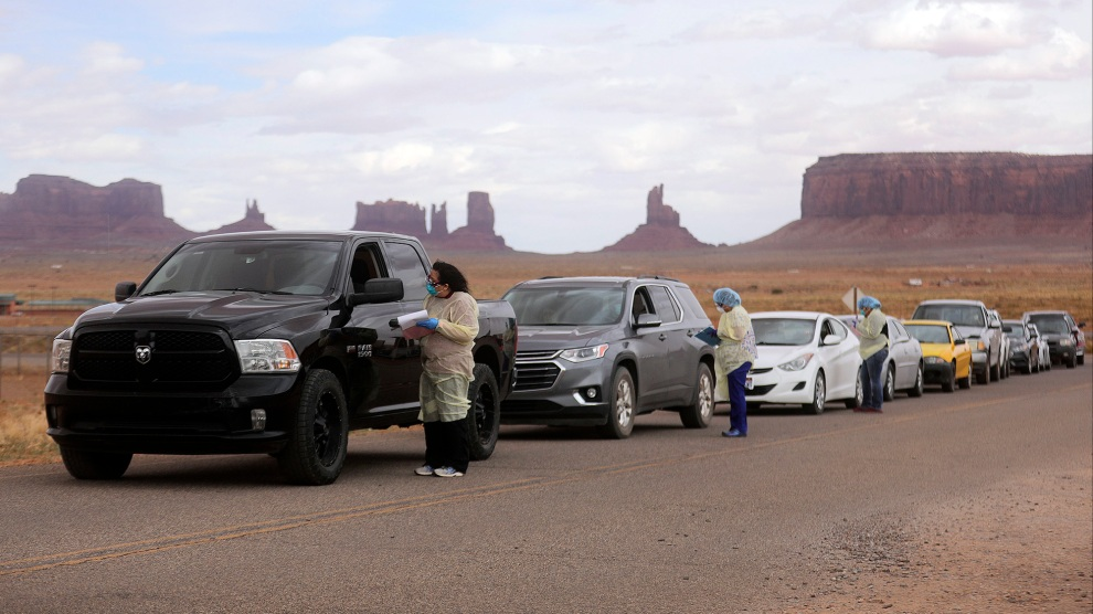 Korene Atene, a nursing assistant, gets information from people lined up to get tested for COVID-19 in Oljato-Monument Valley, Navajo Nation.Kristin Murphy/The Deseret News/AP