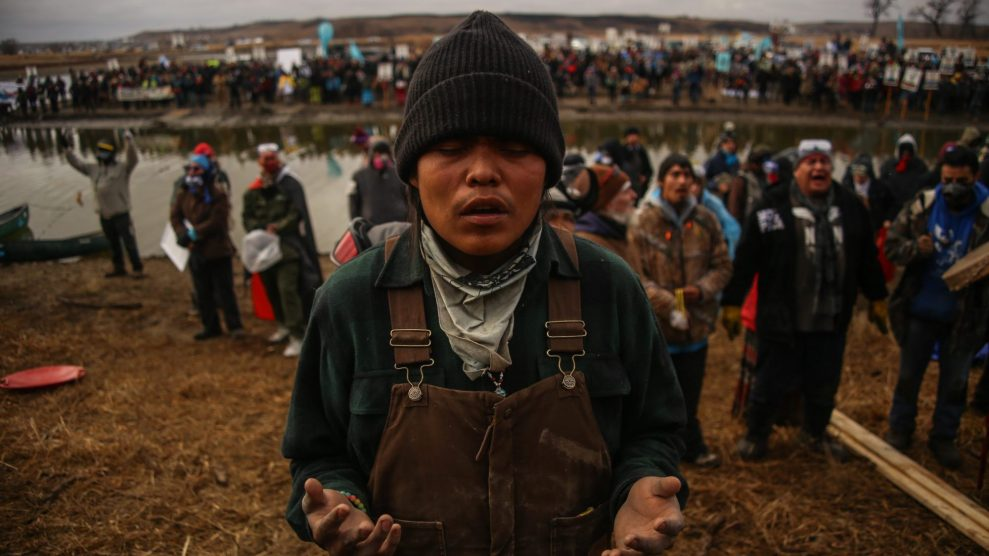 A water protector prays as he and others defend a sacred site at the Standing Rock Indian Reservation in 2016.  Joel Angel/Zuma
