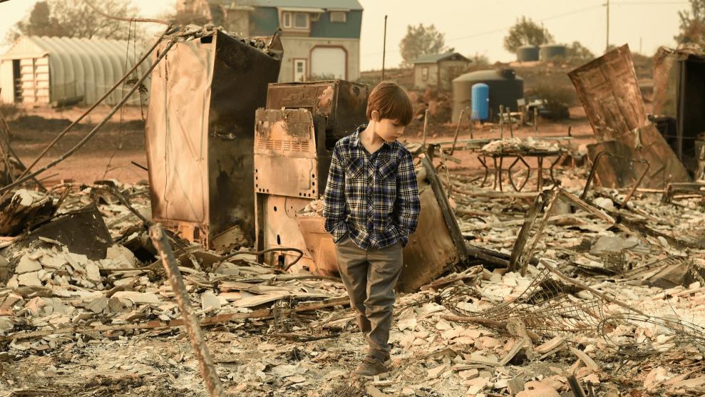 A young boy surveys the brown wreckage of a home