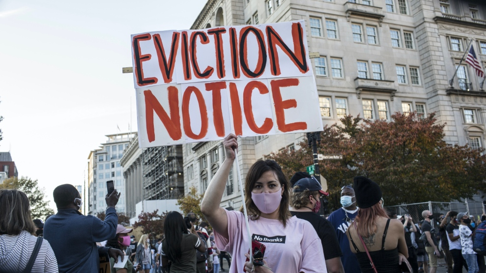 A woman holding a sign with EVICTION NOTICE written on it, stands at Black Lives Matter Plaza near the White House