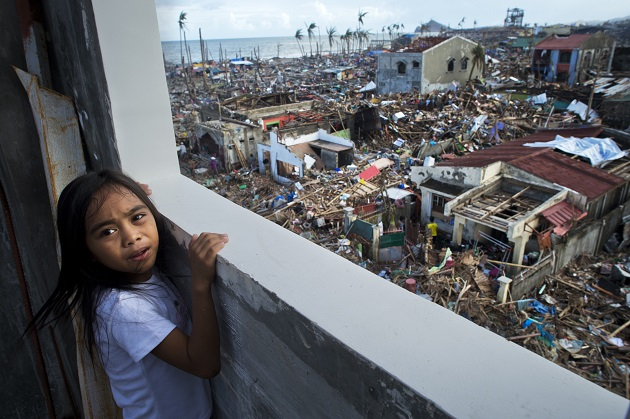 A young girl looks out over the devastated town of Tanauan in Leyte province, the Philippines.