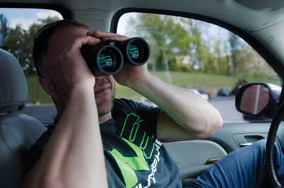 A guy in a car with binoculars