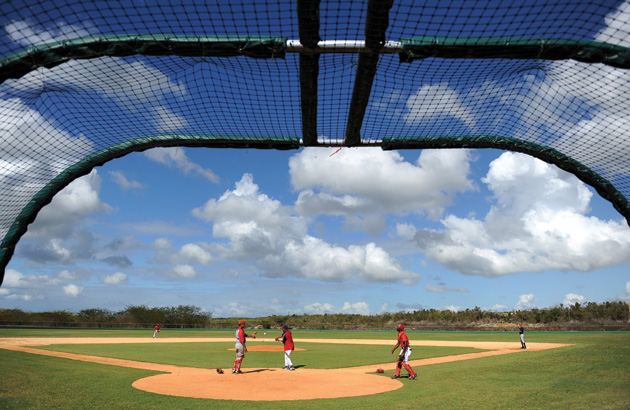 A Nationals scout, center, runs drills with local players during a tryout at the Complex de las Américas in February 2011 in Boca Chica.