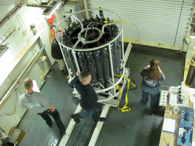 Jeremy Mathis (center) and others get ready to take samples from the CTD just brought back aboard from its trip to the bottom. Julia Whitty