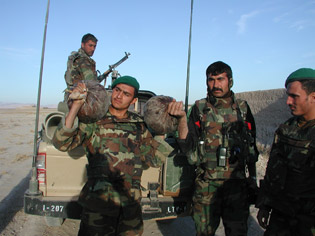 Afghan National Army soldiers display more than six kilograms of opium discovered in a former insurgent safe house in the Farah province of Afghanistan Dec. 16, 2007. (Photo courtesy of Combined Joint Special Operations Task Force - Afghanistan)