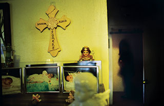 A wooden cross made by a friend hangs in one of the Romero household's two shrines to baby America, who died at five months.